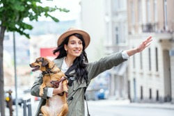 Young woman with dog waving to stop a taxi on the street. young female with funny dog stretching out arm and catching taxi while standing on roadside in city