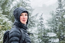 Young woman with down jacket stands in front of fir trees. First snow of the season covers the branches of the trees.