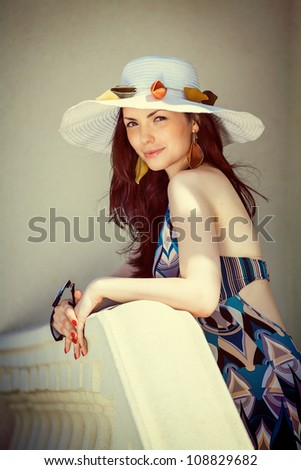 Young woman with elements of paste on hat