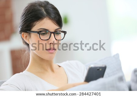 Young woman with eyeglasses reading message on phone