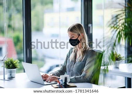 Young woman with face mask back at work in office after lockdown, using laptop.