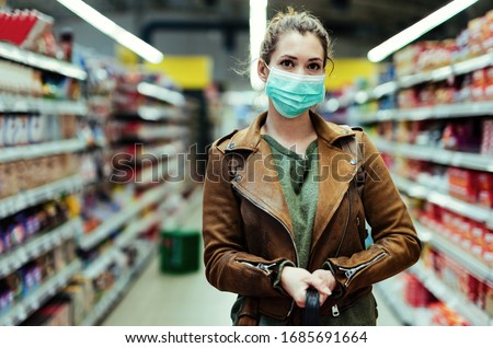 Young woman with face mask standing at supermarket aisle while buying during virus pandemic.