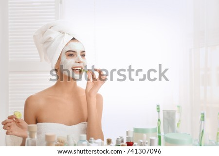 Young woman with facial mask and cucumber slices in bathroom