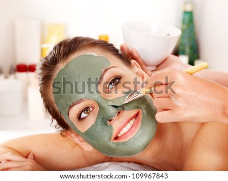 Young woman with facial mask in beauty spa. - stock photo