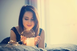 Young woman with fairy lights dreaming in bed