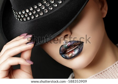 Stock Photo Young woman with fashion make up hiding her eyes under black hat. Fashion beauty portrait. Modern makeup. Dark lips with colorful metallic tints. Studio shot