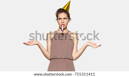 Young woman with festive hat and whistle at party fills disappointment. Festive girl with emotion of misunderstanding on her face. Concept of the holiday or birthday party.