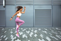 Young woman with fit body jumping and running against grey background. Female model in sportswear exercising outdoors. Modern young woman in sports clothing jumping while exercising outdoors