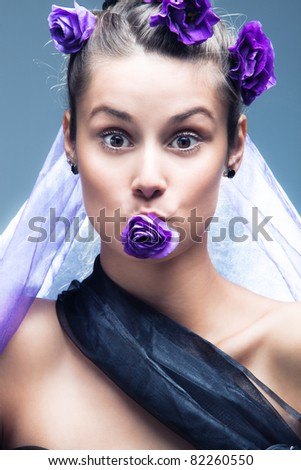 young woman with flower in hair and mouth, studio shot