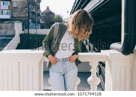 Young woman with fluttering blonde hair standing next to a bridge parapet looking down. Candid lifestyle photo of fashionable female posing on city street at sunny spring day.