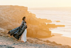Young woman with flying blanket standing on cliff's edge and looking to the ocean on sunset. Wanderlust concept.