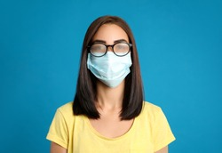 Young woman with foggy glasses caused by wearing disposable mask on blue background. Protective measure during coronavirus pandemic
