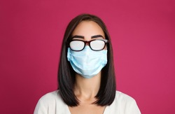 Young woman with foggy glasses caused by wearing disposable mask on pink background. Protective measure during coronavirus pandemic