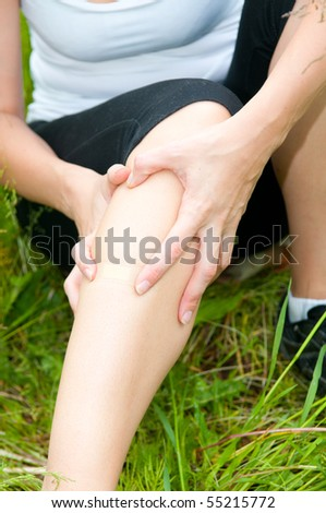 young woman with foot trauma in  field - stock photo