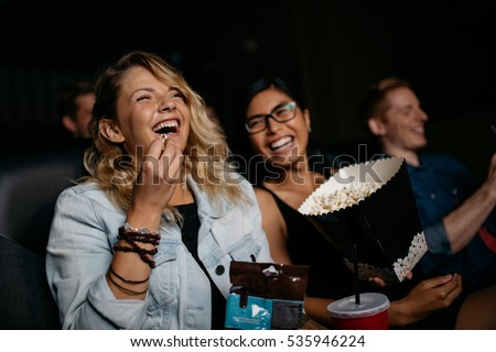 Photo of  Young woman with friends watching movie in cinema and laughing. Group of people in theater with popcorns and drinks.