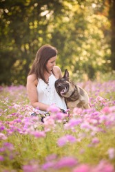 Young woman with German Shepherd dog in the gorgeous summer field