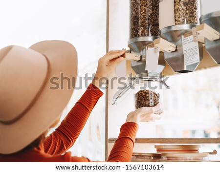 Young woman with glass jar buying bulk foods in zero waste shop. Dispensers for cereals and grains in plastic free grocery store. Sustainable shopping at small local businesses. Eco Bio Organic Food