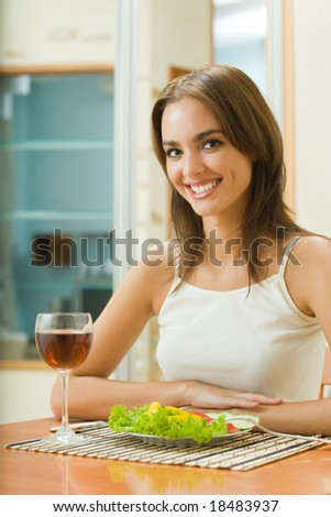 Young woman with glass of redwine and salad at home