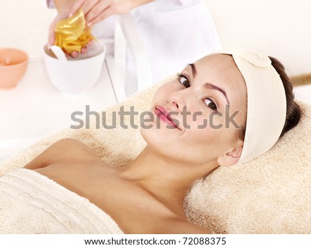 Young woman with gold facial mask.