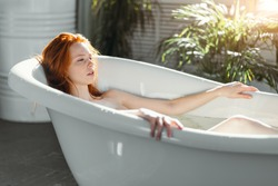 Young woman with gorgeous red hair getting spa treatment at beauty salon, relaxing in bathtub with green plants and flowers on background. Bodycare and Relax concept