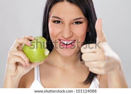 Young woman with green apple and showing thumb up, healthy eating