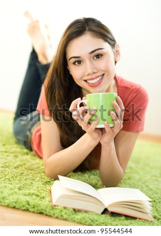 Young woman with green cup and book at home