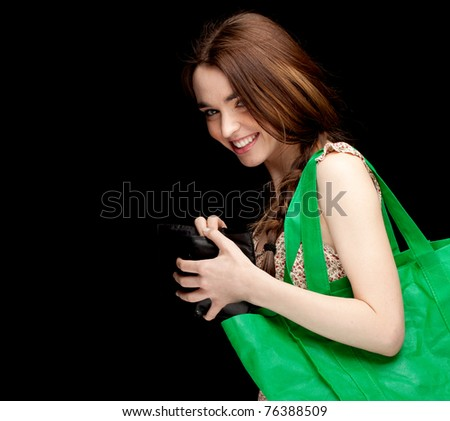 young woman with green ecological shopping bag, black background