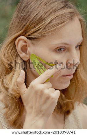 Young woman with green tapes on face. Face aesthetic taping. Attractive young woman with kinesiology tapes on forehead. Beautiful Woman With Kinesiology Facelift Tapes
