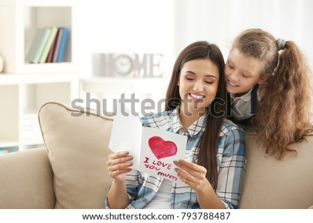 Young woman with greeting card from her daughter indoors. Mother's day celebration #793788487