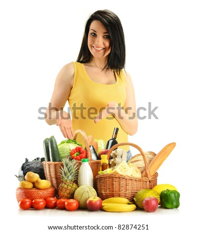 Young woman with groceries in wicker baskets isolated on white. Variety of products including vegetables, fruits, dairy, wine and bread