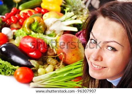 Young woman with group of fruit and vegetables.