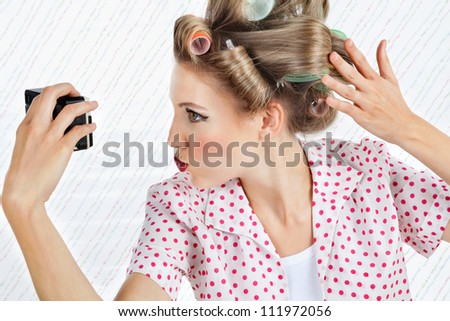 Young woman with hair curlers puckering while taking a self portrait through a vintage camera