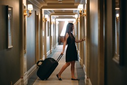 Young woman with handbag and suitcase in an elegant suit walks the hotel corridor to her room