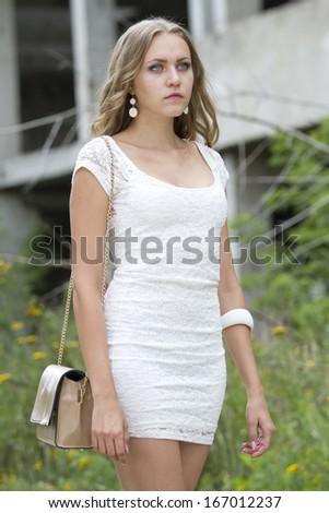 young woman with handbag walking on the street - stock photo