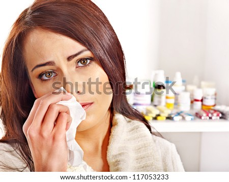 Young woman with handkerchief having  tablets and pills.  Indoors. - stock photo