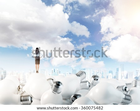 Young woman with hands on hips standing on huge scattered bulbs. Blue sky at the background. Back view. Concept of new ideas. #360075482