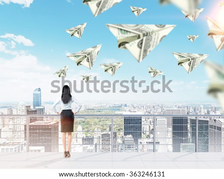 Young woman with hands on hips thinking about money and opportunities, dollar planes flying around. City panorama at the background. Back view. Concept of getting a fortune.