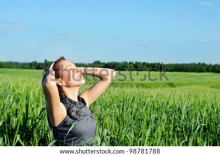 young woman with hands raised up in the wheat field over blue sky in summer