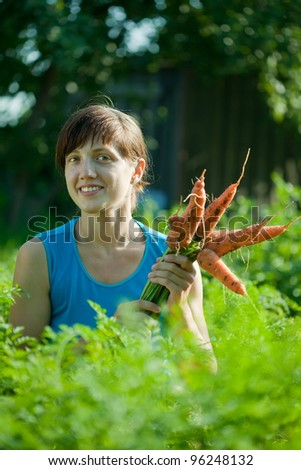 young woman with harvested carrot in field