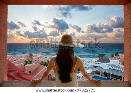 Young woman with hat looking at the beach and sky from a balcony
