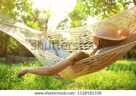 Young woman with hat resting in comfortable hammock at green garden Foto d'archivio ©