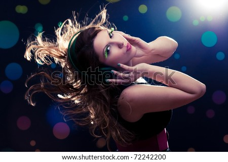 Young woman with headphones and flying hair