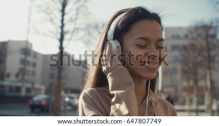 Young woman with headphones enjoying time in a city. #647807749