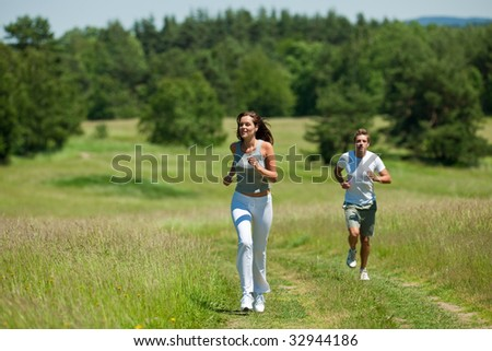 Young woman with headphones jogging, man in background, shallow DOF