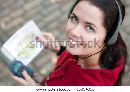 Young woman with headphones, listening to audio guide
