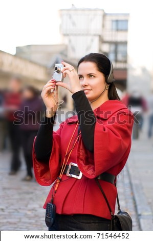 Young woman with headphones, listening to audio guide taking pictures