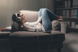 Young woman with headphones relaxing at home late at night, she is lying on the armchair and listening to music using a tablet