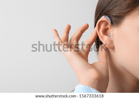 Young woman with hearing aid on light background ストックフォト ©