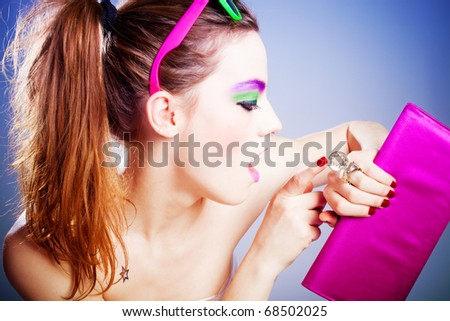 young woman with heavy make up looking at watch  in the form of ring, studio shot
