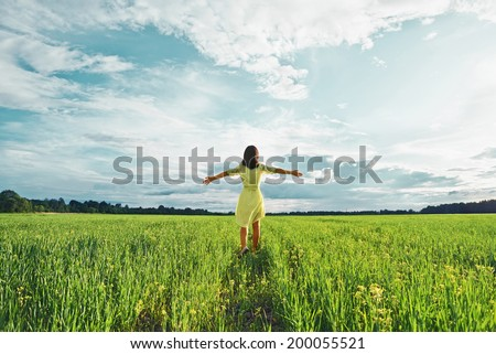 Young woman with her arms wide spread is enjoying in the sunny summer day, rear view